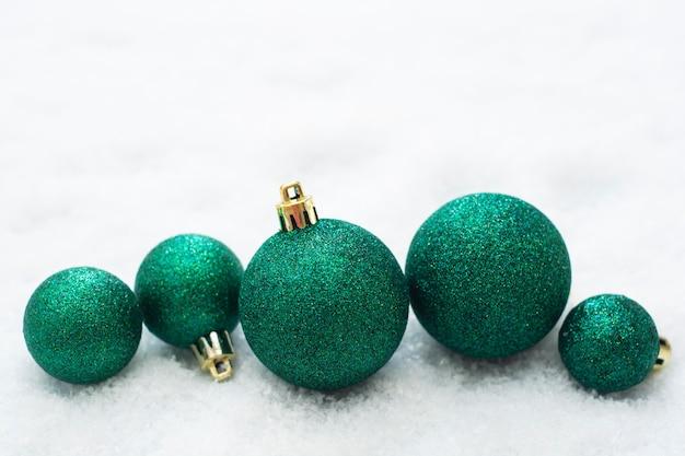 O natal brilhou enfeites verdes isolados na neve. cartão de inverno.