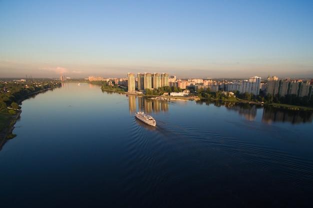 O navio está no rio ao pôr do sol. ele flutua lentamente ao longo do rio nos raios do sol poente