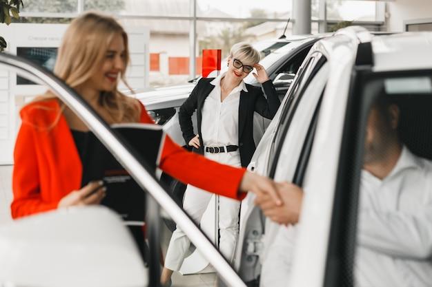 O negociante e o comprador de automóveis agitam as mãos que fazem um acordo. .