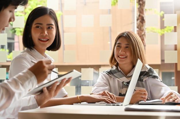 O negócio consulta com os executivos novos que encontram-se na tabela de trabalho e na tabuleta digital nas mãos.