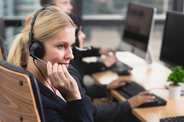 O negócio de sorriso do operador do apoio ao cliente team nos auriculares que trabalham no escritório.
