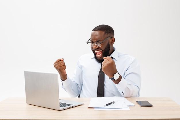 O negócio é a vida dele. alegre jovem africano em roupa formal e trabalhando no laptop