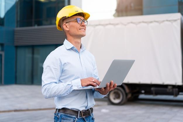 O negócio. engenheiro capacete de proteção para uso do laptop controles de controle do processo de trabalho inspetor supervisor óculos de capacete amarelo empresa de transporte prédio de escritórios e fundo de caminhão