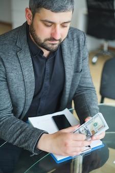 O negócio. homem de negócios, sentado a mesa e assinatura do contrato. homem leva suborno para assinar o contrato. alta resolução