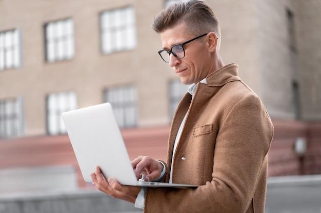 O negócio. homem de negócios usando laptop adulto ao ar livre, caucasiano, masculino, empresário, óculos, vendo a tela do notebook, pensando sério, luz solar, fundo, grande, cidade, rua