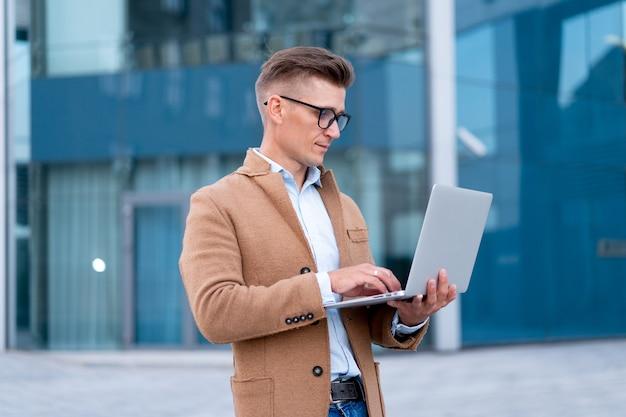 O negócio. homem de negócios usando laptop adulto ao ar livre, caucasiano, masculino, pessoa de negócios, óculos, vendo a tela do notebook, pensando sério, fundo sanlight, grande, cidade, rua