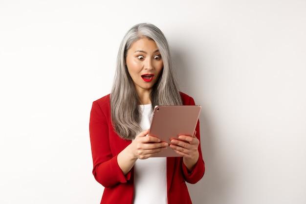 O negócio. mulher asiática sênior olhando para a tela do tablet digital com rosto espantado e surpreso, lendo notícias incríveis online, em pé sobre um fundo branco.