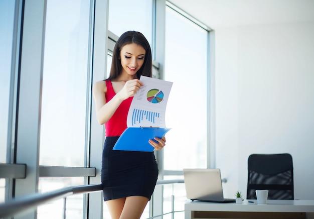 O negócio. mulher bonita fala por telefone. trabalha no escritório da luz e segura a pasta nas mãos