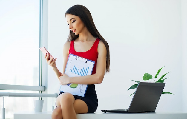 O negócio. mulher de negócios jovem sentada na mesa do escritório grande luz. garota vestida de camiseta vermelha e saia preta. segurando na pasta de mão. alta resolução