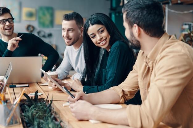 O negócio não é enfadonho. grupo de jovens modernos em roupas casuais inteligentes discutindo algo e sorrindo enquanto trabalhavam no escritório criativo