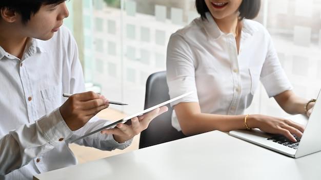 O negócio novo consulta e reunião na tabela de trabalho e na tabuleta digital nas mãos.