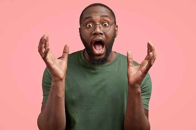 O negro surpreso e impressionado abre a boca amplamente, segura plams perto do rosto, fica chocado e surpreso