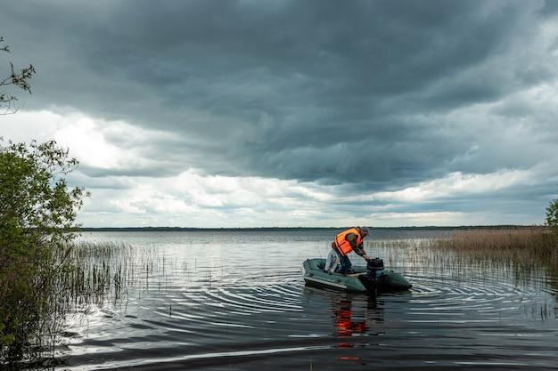 O neto e o avô pescam juntos de um barco no lago.