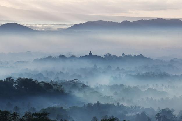 O nevoeiro azul durante o nascer do sol no templo de borobudur, indonésia