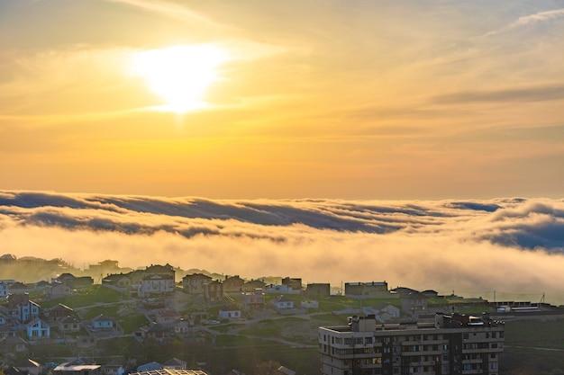 O nevoeiro está baixo sobre a cidade. pôr do sol com névoa sobre a cidade, bela paisagem. rússia, krasnodar krai, arredores da cidade turística de anapa