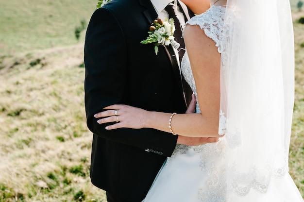 O noivo abraça a noiva com as mãos atrás da cintura e em pé na cerimônia de casamento ao ar livre no quintal da natureza.