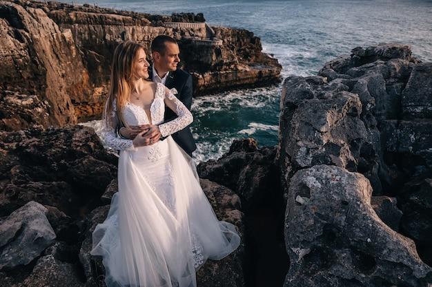 O noivo abraça a noiva e ela sorri no fundo das pedras e do mar