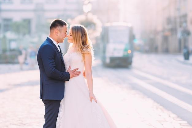 O noivo abraça a noiva e eles fecham os olhos.