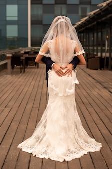 O noivo abraça a noiva e faz um coração com os dedos