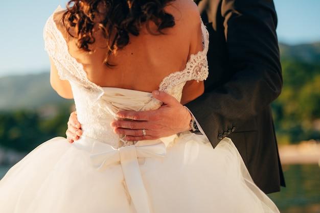 O noivo abraça a noiva no casamento na praia