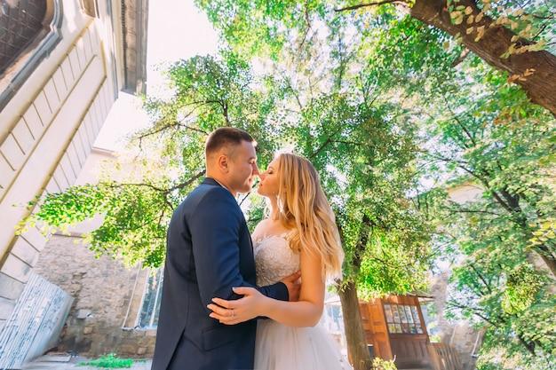 O noivo abraça a noiva pela cintura e ela balança os cabelos.