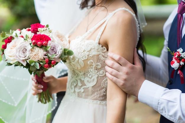 O noivo abraça delicadamente o ombro da noiva, close-up