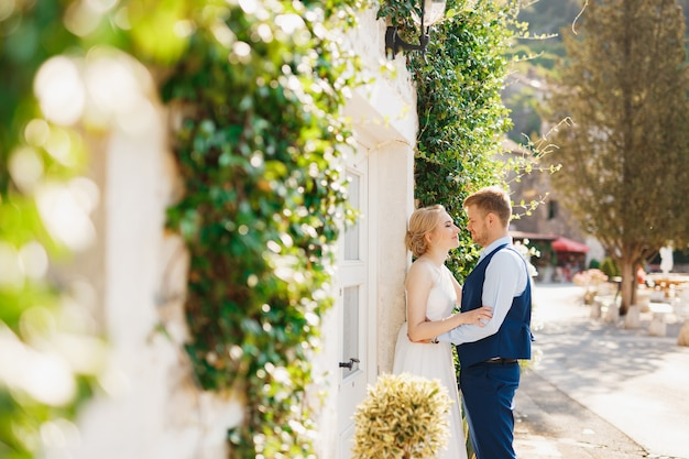 O noivo abraça gentilmente a noiva contra o fundo de uma bela cerca branca coberta de hera