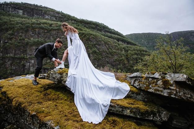 O noivo ajuda a noiva amarrando o laço na bota. retrato de um casal de noivos em pé sobre uma rocha.