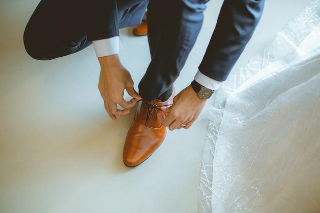 O noivo amarra sapatos de couro no chão