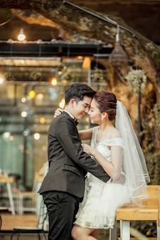 O noivo asiático e a noiva asiática estão próximos e estão prestes a se beijar com um rosto sorridente e feliz.