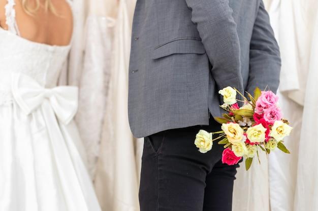 O noivo caucasiano dá a noiva da flor no estúdio do casamento.