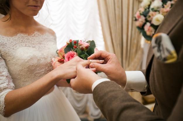 O noivo coloca o anel na mão da noiva. as mãos dos recém-casados.
