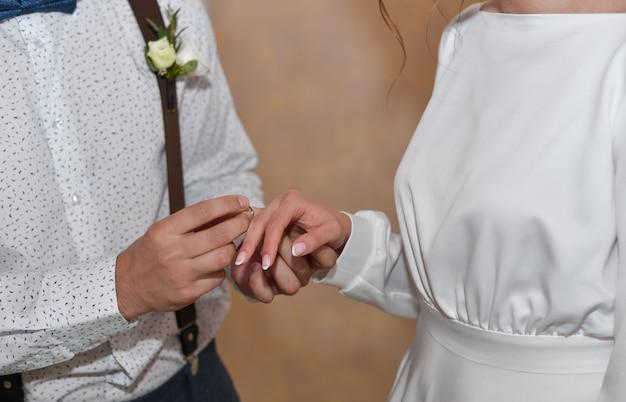 O noivo coloca o anel no dedo da noiva no casamento