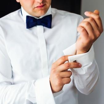 O noivo com gravata borboleta coloca abotoaduras nas camisas de manga branca. perto