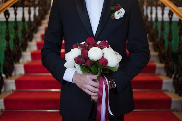 O noivo com o buquê de noiva encontra sua futura esposa, close-up de peônias vermelhas e brancas