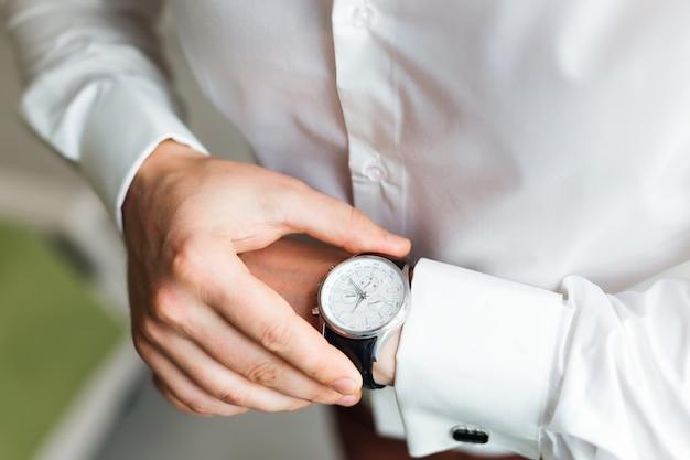 O noivo de camisa branca olha para o mostrador do relógio de pulso