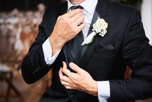 O noivo de elegnat no terno à moda preto que põe sobre um laço na manhã antes do casamento.