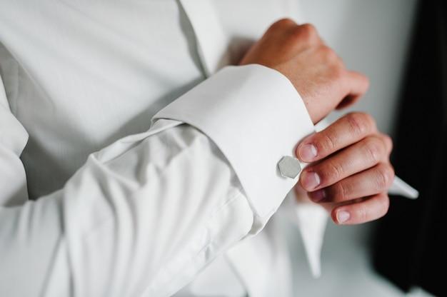 O noivo de mão usa um botão de punho de prata metálico. manhã de casamento.