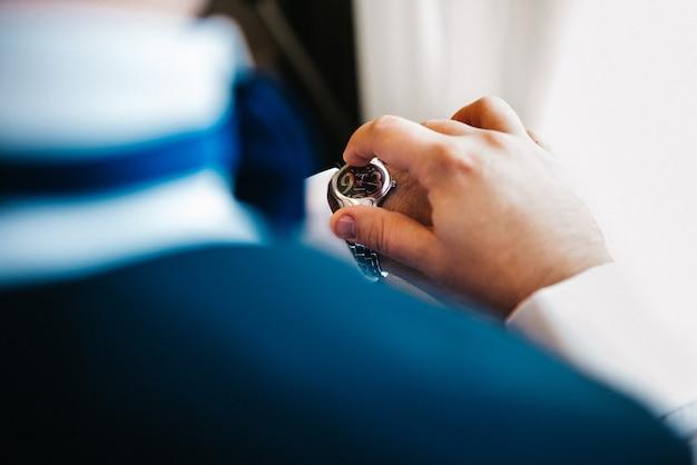 O noivo de terno azul olha para o relógio usado em sua mão esquerda