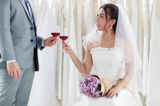 O noivo de terno cinza está dando à noiva uma taça de vinho para a noiva em um vestido de renda branca no dia do casamento para comemorar com alegria. o melhor dia de amor de conceito.