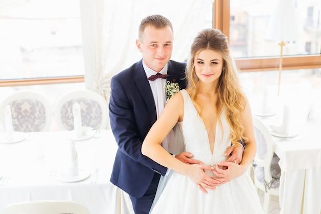 O noivo de terno e gravata borboleta abraça a noiva pela cintura e ela olha para a câmera