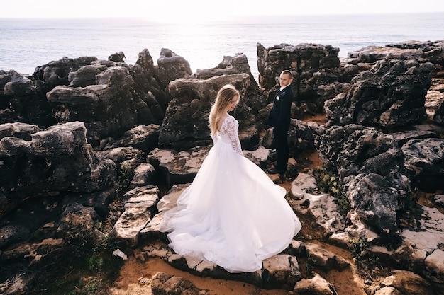 O noivo de terno olha para a noiva de vestido branco
