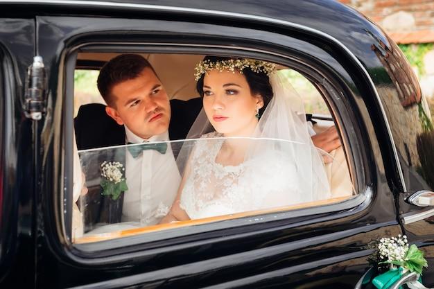 O noivo de terno olha para uma linda noiva em um vestido de noiva e eles estão sentados em um carro