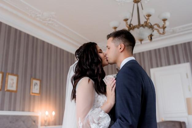 O noivo e a noiva caucasiana estão beijando ternamente no quarto de hotel claro