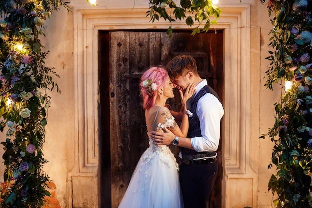 O noivo e a noiva com o cabelo rosa estão diante de uma porta com guirlandas de flores e luz