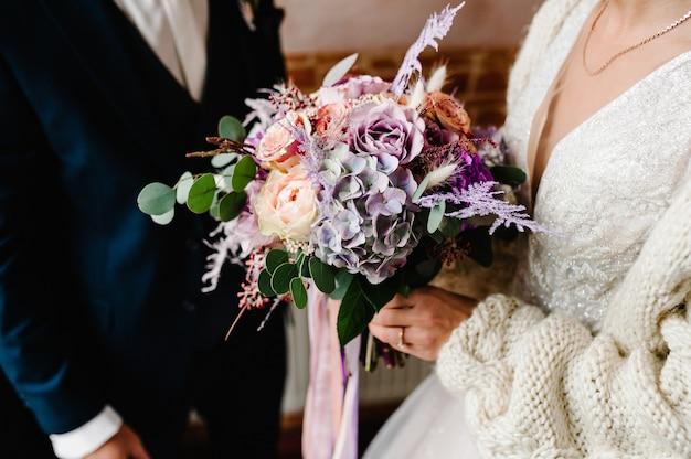 O noivo e a noiva com um buquê de casamento nas mãos.