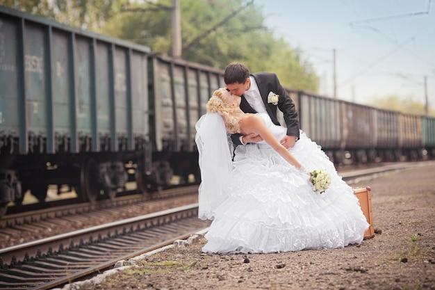 O noivo e a noiva com uma mala na estação ferroviária