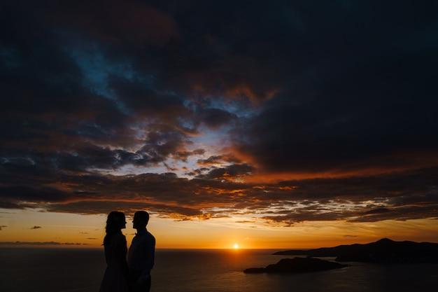 O noivo e a noiva dão as mãos ao pôr do sol, contra o fundo do mar