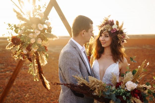 O noivo e a noiva jovem e bonita se amam. dia do casamento no estilo boho.