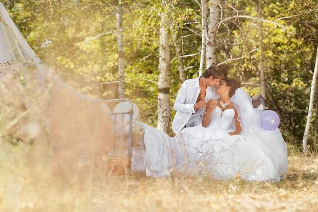 O noivo e a noiva na floresta em uma cama